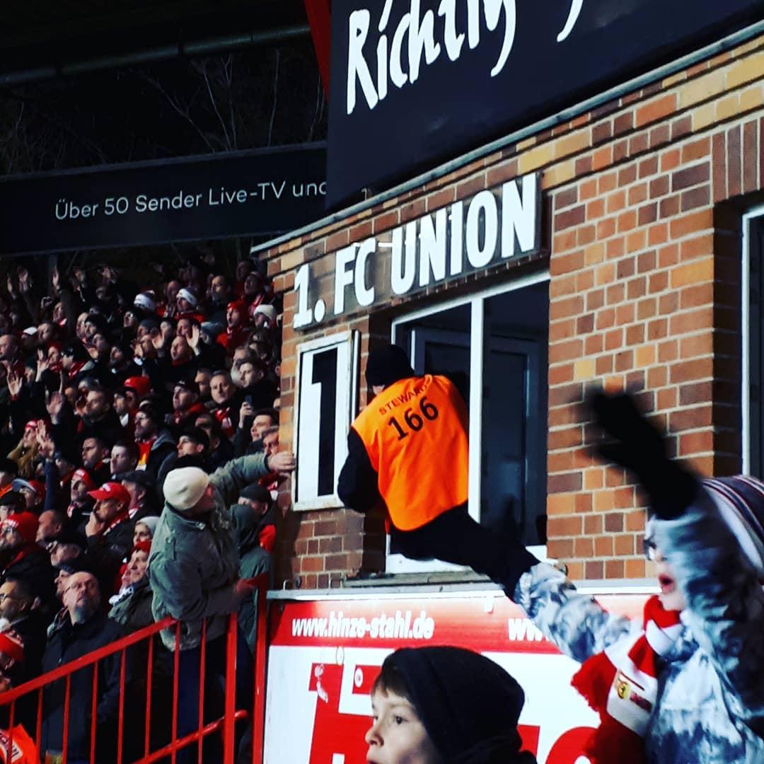 Gemeinsam für die 2: Ein Zuschauer und ein Stadionmitarbeiter bemühen sich minutenlang, die festgeklemmte 1 an der Anzeigetafel des 1. FC Union zu befreien, Foto: Nadine Kittner