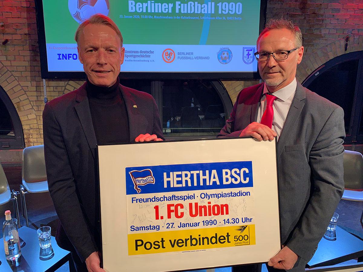 Olaf Seier (früher Kapitän und Stürmer des 1. FC Union Berlin) und Theo Gries (früherer Stürmer von Hertha BSC) halten das Plakat zum Wiedervereinigungsspiel, Foto: Sebastian Fiebrig
