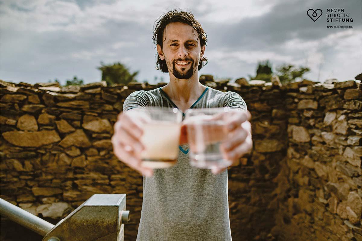 Neven Subotic hält sauberes und verdrecktes Wasser zum Vergleich in die Kamera, Foto: Neven-Subotic-Stiftung